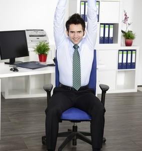 Junger Manager macht Yoga am Arbeitsplatz im Bro